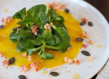 Ein farbenfrohes Carpaccio aus gelber Bete mit Feldsalat und säuerlicher Apfelvinaigrette.