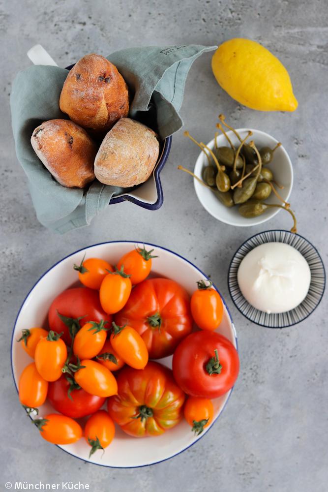 Hier sieht man fast alle Zutaten für den Panzanella. Tomaten, Brot, Kapern, Zitrone und Burrata.