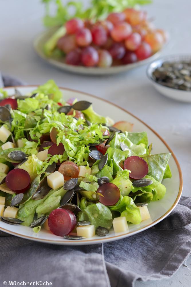 Knackiger Salat mit Trauben, Käse und Kürbiskernen.